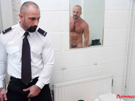 Beefy male guard walking in on a hairy muscular nude man in prison.