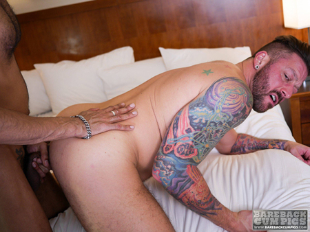 Tattooed muscle Daddy taking a big black cock in his ass raw.