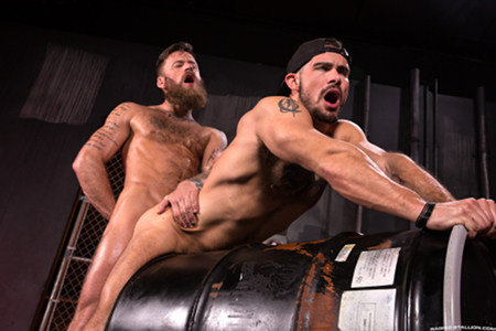 Hairy muscle hunks having gay sex over a barrel.