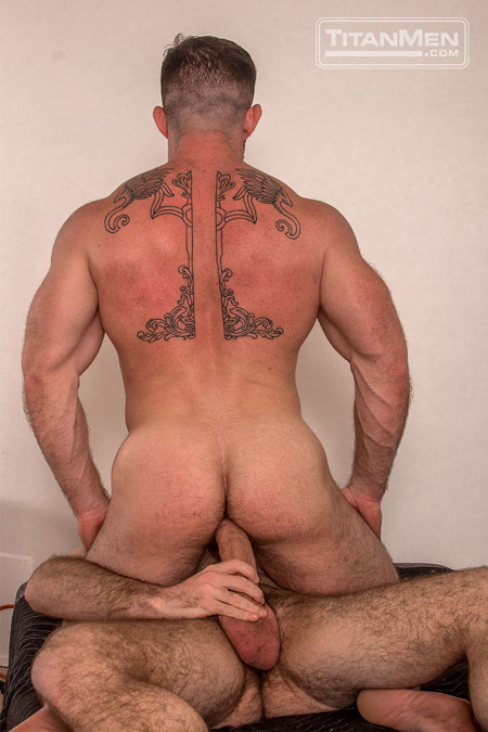 Giant tattooed muscle man sitting on a big uncut cock.