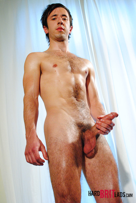 Hairy twink holding his huge hard cock in his hand.