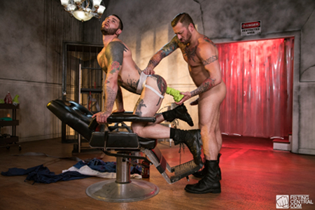 Tattooed muscle Daddy stuffing a giant dildo into his male slave.