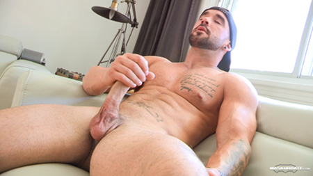 Tattooed bodybuilder stroking his huge cock in front of another man.
