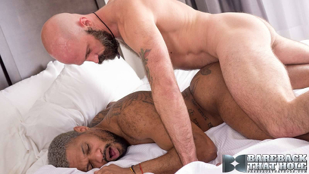 Tattooed, grey-haired black muscle man getting fucked bareback by a bald, muscular Daddy.