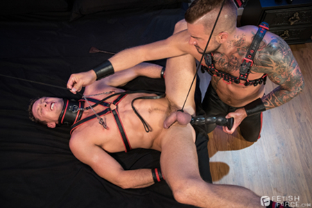 Gay leather BDSM with a giant dildo.