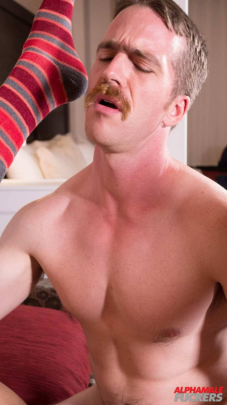 Muscular hunk with a red mustache fucking another man.