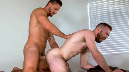 Hairy muscular stud getting fucked in the ass by a mature bearded man.