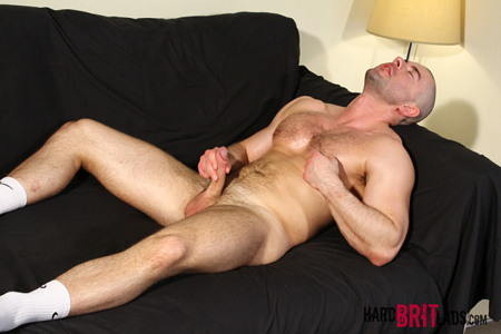 Thick muscular guy in nothing but athletic socks masturbating on the couch.