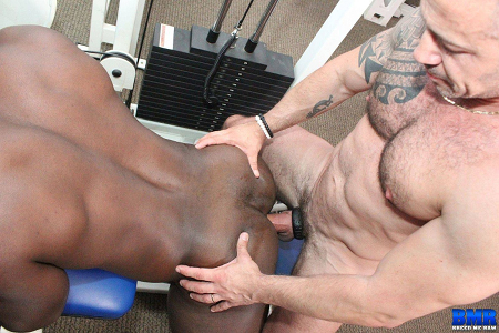 Hairy bodybuilder fucking his black workout partner bareback at the gay gym.
