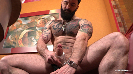Heavily tattooed bodybuilder masturbating with a masturbation sleeve.