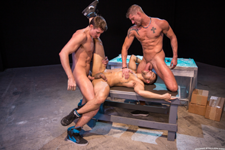 Muscular power bottom being gay spit-roasted by two muscle hunks.