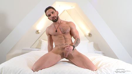 French muscle hunk masturbating in bed.