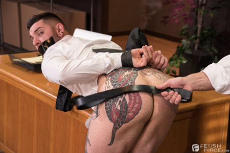 Men in suits practicing gay BDSM with a mouth gag and belt spanking.