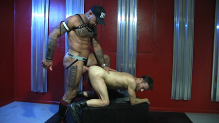 Tattooed muscle Daddy in leather fucking his bottom boy bareback.