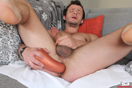 Muscle jock fucks himself in the ass with a giant dildo.
