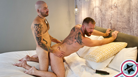 Hairy ginger cub being fucked in the ass raw by another heavily tattooed man.