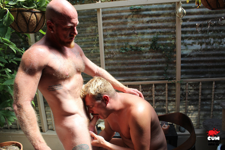 Mustachioed blonde man sucking the pierced cock of a hairy ginger Daddy.