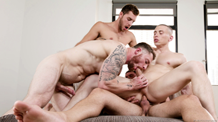 Tattooed muscle studs fucking each other bareback in a gay group sex session.