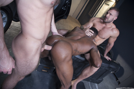 Two white muscle hunks spit-roast a muscular, tattooed black man.