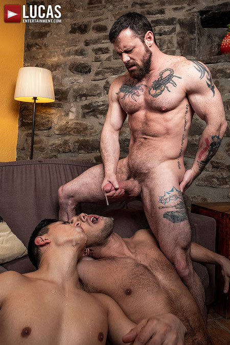 Hairy muscle stud cumming in the faces of two men.