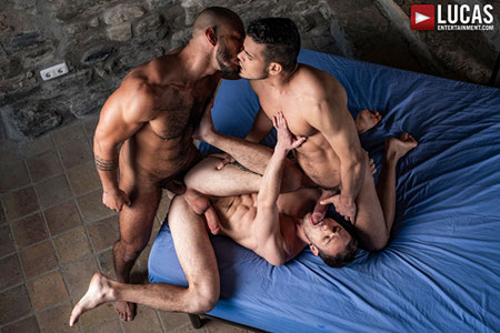 Gay hunk being spit-roasted bareback by two macho men.